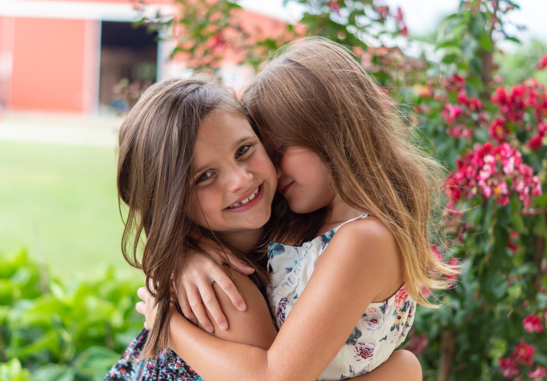 close up photo of two little girls hugging each other