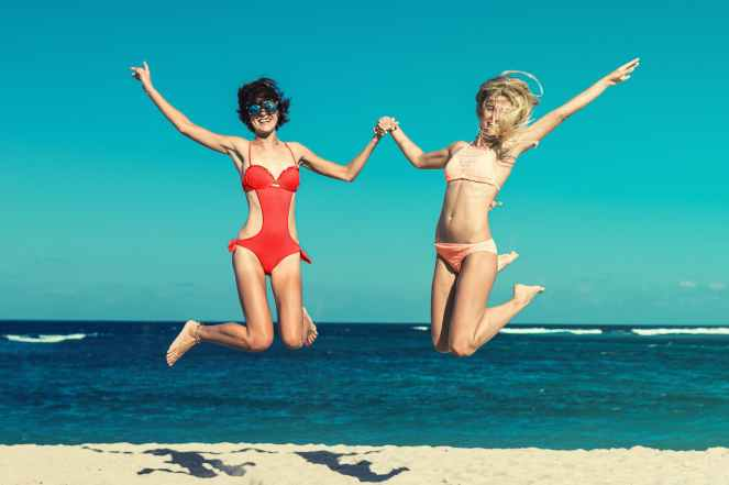two woman in bikini jumping